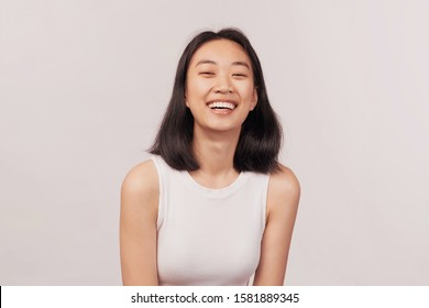 Girl laughs at something funny closes eyes with pleasure. Businesslike young woman Asian appearance with black hair and brown eyes dressed in short shirt stands isolated white background in Studio.
