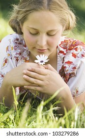 Girl laying down on green grass, smelling a daisy flower and smiling.