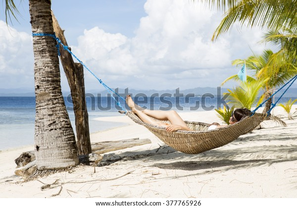 A girl laying in the hammock at a beautiful beach.