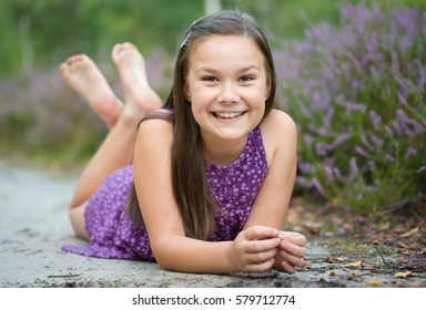 Girl is laying on forest road and playing, outdoor shoot