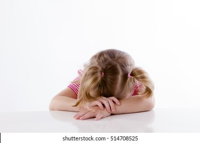girl lays her head on the table, upset depressed. White background. studio
