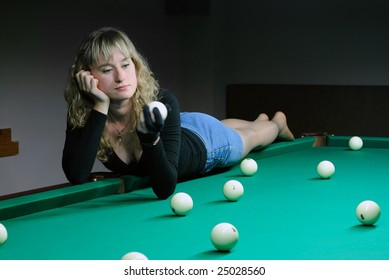 The girl lays on a billiard table and looks on the ball