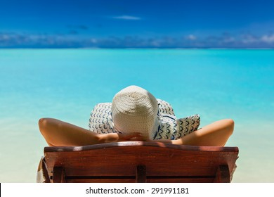 girl lays on a chaise lounge in the back on the banks of the turquoise Caribbean sea on Bahamian Maldivian Hawaiian beaches. Girl looking at beach in Formentera turquoise Mediterranean sea background