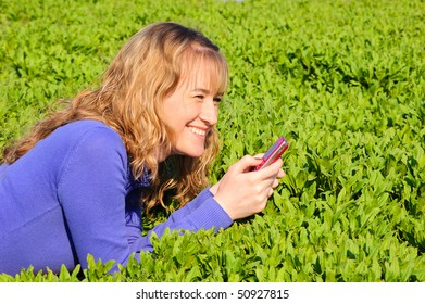 The girl lays on a green grass and reads sms