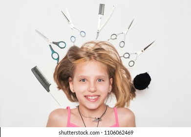 The girl lays on a white background among professional tools for haircuts - scissors and combs lie near her head. The girl is happy and smiles because she recently cut and made a hairstyle kare
