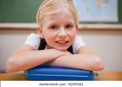 Girl leaning on her desk in a classroom
