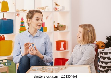 Girl learning alphabet during classes with speech therapist in the school