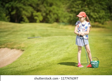 The girl is learning to play golf