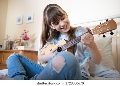 Girl Learning To Play Ukulele Sitting On Bed In Bedroom