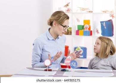 Girl learning traffic regulations with child psychologist in compensatory classes