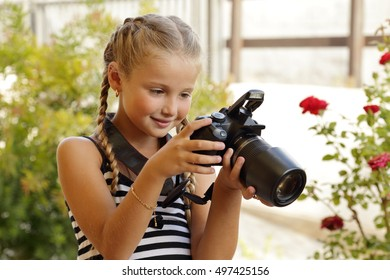 Girl learning to use a camera