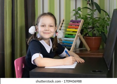 A girl learns lessons, does homework, a schoolgirl studies at home at the table. Writes in notebooks on the table. Looks at the teacher.