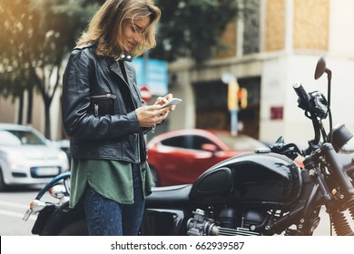 Girl in leather jacket holding smart phone on background motorcycle in sun atmospheric city, hipster using in female hands and text mobile, street lifestyle, tourist planing route in summer concept