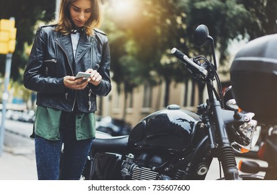 Girl in leather jacket holding smart phone on background motorcycle in sun flare atmospheric city, hipster using in female hands and texting mobile, motorbike street lifestyle, tourist planing route