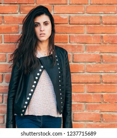 girl in leather jacket on brick wall background upset