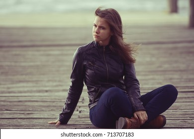 girl in a leather jacket sits outside the rustic style