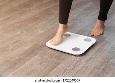 a girl in leggings wants to stand with one foot on the scales. concept of frustration with seen weight.