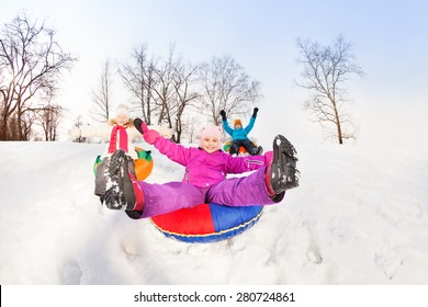 Girl with legs up and friends slide down the hill