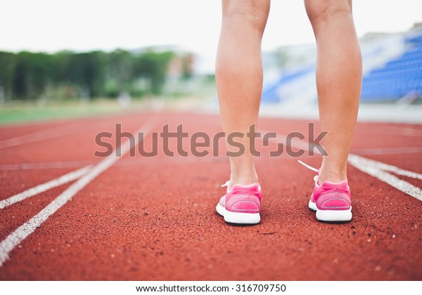 Girl legs in sport shoes standing on a running track with stadium stands and football field on background. Calf cropped back view