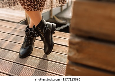 Girl in a leopard skirt and black boots in hard light on a concrete floor. Light key on boots