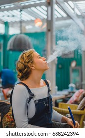 The girl lets out smoke from a hookah