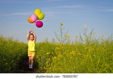 Girl letting go balloons flying in the sky. Happy child waving hand