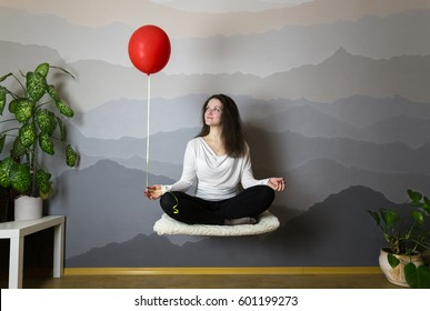 Girl levitates on a hot air balloon in the room, flight in a lotus pose