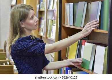 The girl - librarian looking for a reserved book