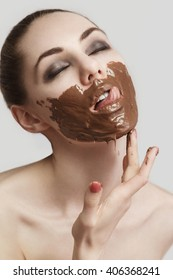 the girl licking the smeared chocolate from lips