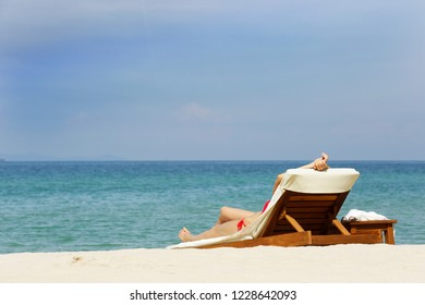 a girl lie down on a sunbed in empty and silent beach at Cholburi, Thailand