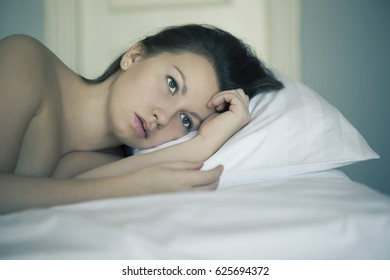A girl lies in bed can't fall asleep thinking and dreaming. Insomnia. Psychology.
