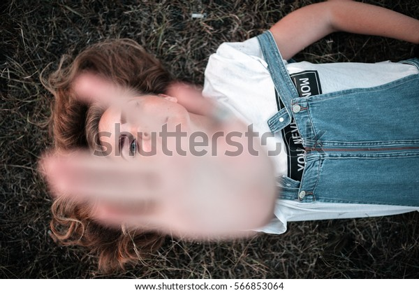 girl lies in the field putting his hand looking through it