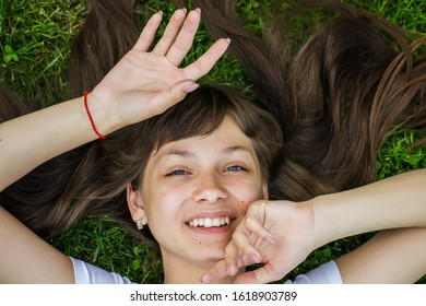 Girl lies with her hair spread out,  outstretched arms on the grass and smiling