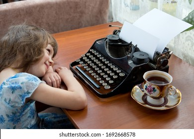 A girl lies next to a typewriter, drinks tea and dreams