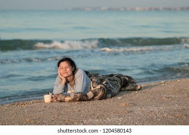The girl lies on the beach with a cup of coffee, cold sleeping bag