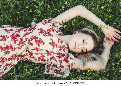The girl lies on the grass. A girl in a white dress is resting on a green meadow. Camping