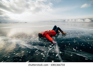 the girl lies on the ice and enjoys the weather. she's having fun. she's happy. girl looks up at the sky