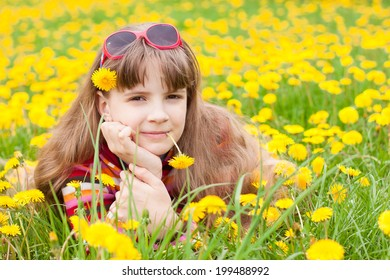 Girl lies on meadow with yellow dandelions