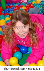 The girl lies on multicolored spheres in a children's attraction
