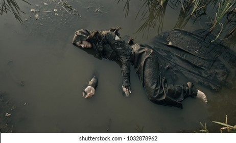 The girl lies in the water. Refugee. Apocalypse.