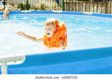 The girl in the life jacket swims in the pool