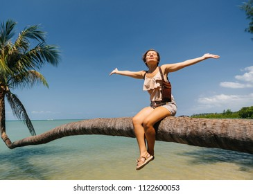 The girl lifted her hands up, resting and sitting on the palm of a tropical island overlooking the sea. Mood and rest.