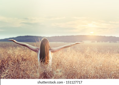 Girl lifting her hands up in the air while saying good bye to another nice day while beautiful sunset.