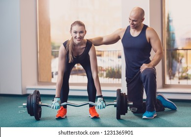 Girl lifts the barbell under the control trainer. The trainer controls the physical exercise of the dvushka with a barbell. Exercise on the strength of the back and arms. Sports equipment for training