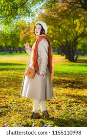 Girl in a light coat and take a sunny autumn day while walking in the park.
