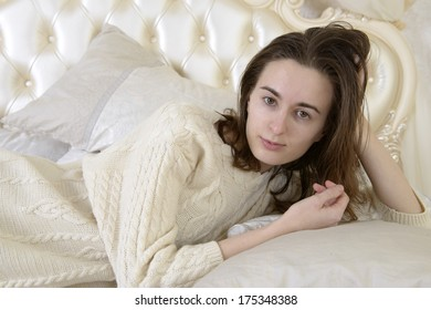 Girl in a light sweater is resting on the large bed