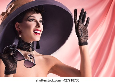 The girl, like a famous actress, wearing a hat and glasses