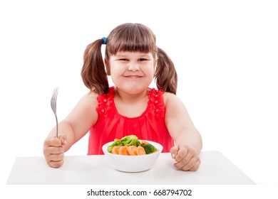 Girl likes healthy food, sits at the table near the plate with vegetables. Child isolated on white background