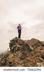 A girl in a lilac jacket looks out into the distance on a mountain, a view of the mountains and an autumnal forest by an overcast day, free space for text