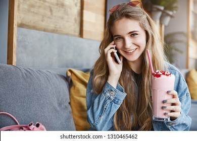 Girl lisening with intrigued and joyful expression story of friend while talking on smartphone, sipping cocktails while gossiping and talking about recent news, smiling broadly at camera